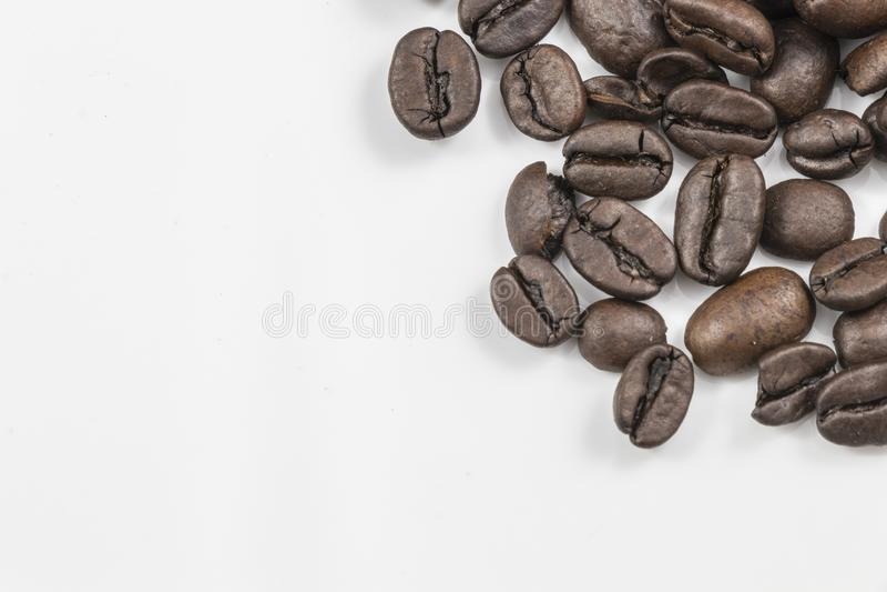 Los granos de café frescos se cierran para arriba con un fondo blanco imagenes de archivo
