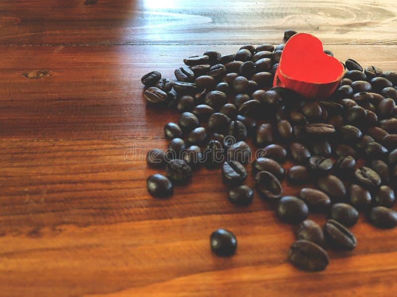 Los granos de café oscuros de la carne asada y el corazón rojo aman fotos de archivo libres de regalías
