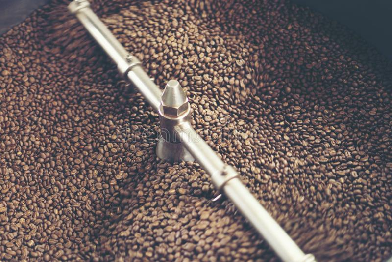 Los granos de café recientemente asados de un bei grande del tostador de café imagen de archivo