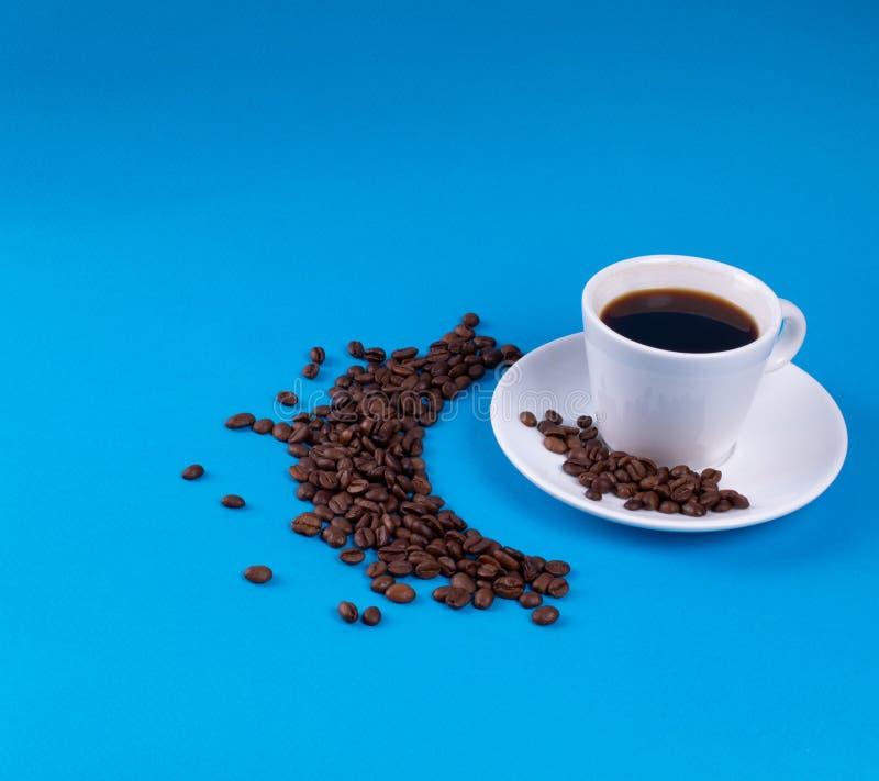 Los granos de café se dispersan en un creciente al lado de China blanca en un fondo azul foto de archivo