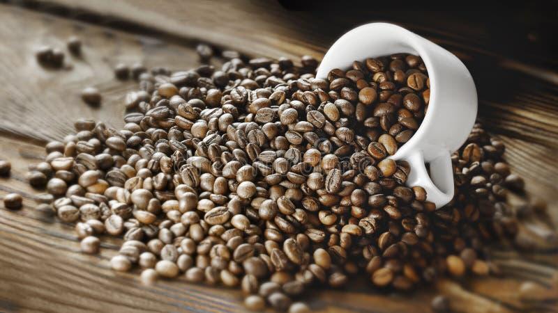 Los granos de café se vierten de una taza en un fondo de madera fotos de archivo