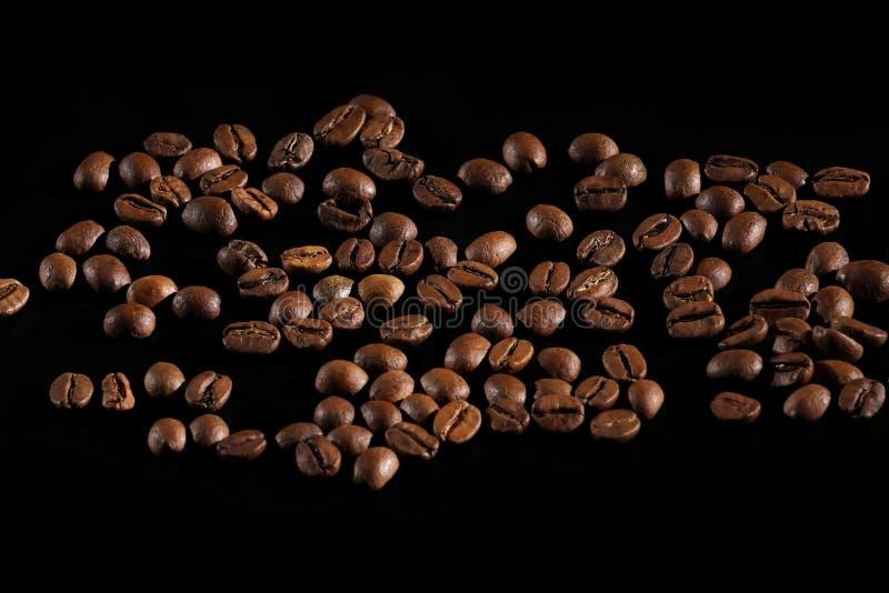 Los granos de caf? asados oscuros arreglaron Primer de los granos de caf? Caf? en un fondo negro imagen de archivo