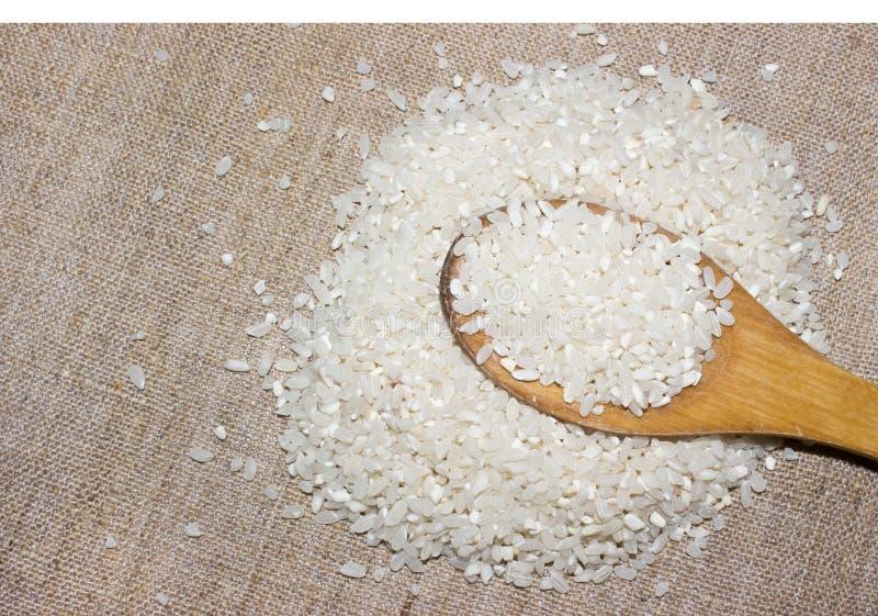 Los granos del arroz blanco son una diapositiva en una cuchara de madera en un viejo pedazo de tela de la lona fotografía de archivo libre de regalías
