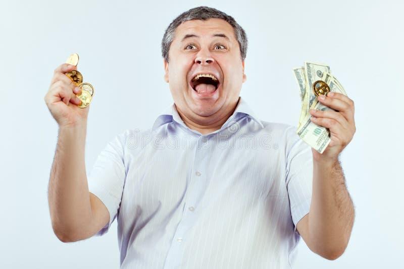 Los gritos del hombre con placer del bitcoin y de dólares, él ganó fotos de archivo