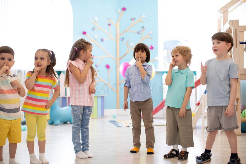 Los grupos de niños de preescolar se divierten y juegan en clases interiores en el jardín de infantes foto de archivo