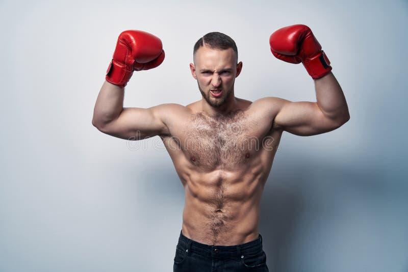 Los guantes de la caja del hombre que llevaban descamisado muscular con las manos aumentaron fotografía de archivo
