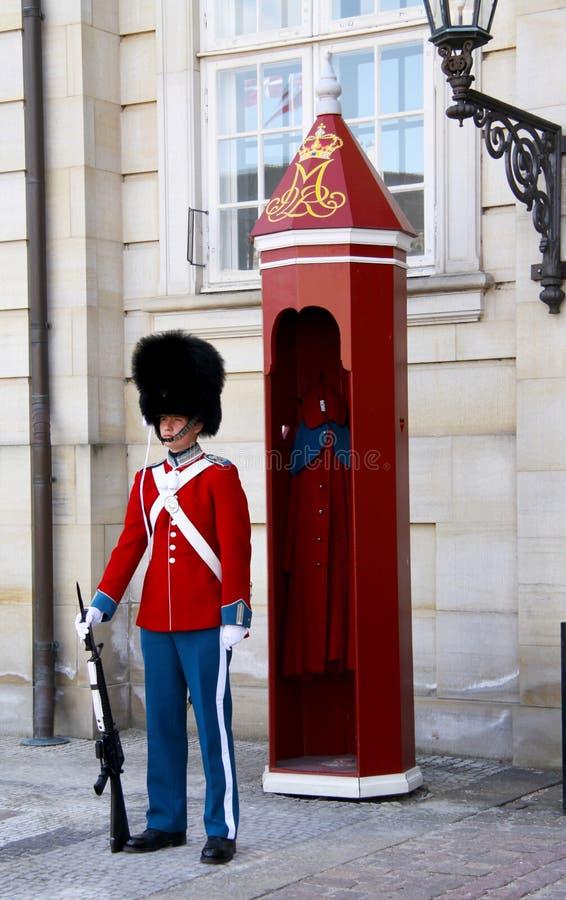 Los guardias del honor en el uniforme rojo de galla que guardan el palacio real de Amalienborg de la residencia en Copenhague, Di fotos de archivo