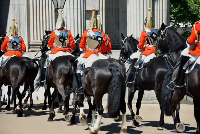 Los guardias reales vestidos a caballo en capas rojas ceremoniales pasan en un desfile en Londres, Inglaterra, Reino Unido foto de archivo libre de regalías