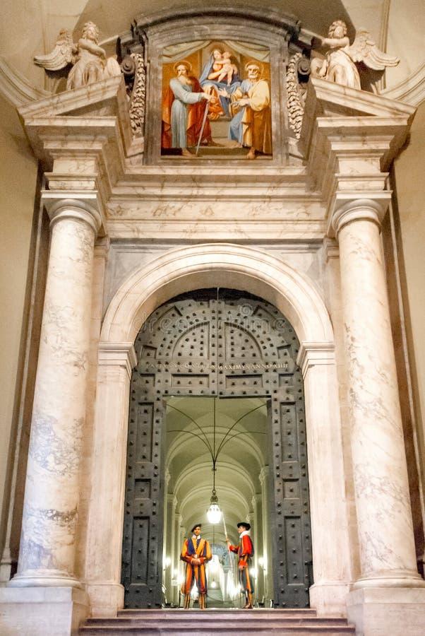 Los guardias suizos se colocan en la puerta de bronce del palacio apostólico II fotografía de archivo libre de regalías