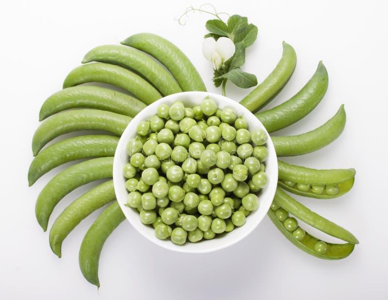Los guisantes verdes frescos en un cuenco blanco, vainas de guisante son cuencos redondos en a foto de archivo