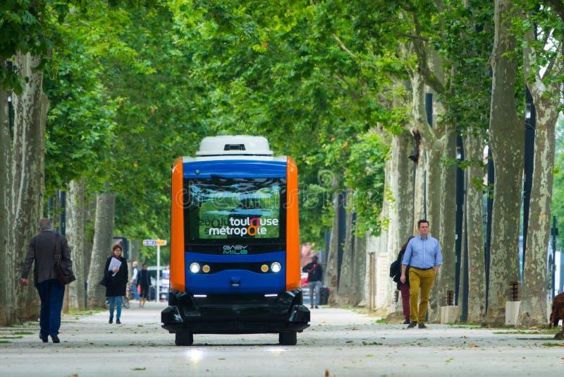 Los habitantes de la ciudad de Toulouse, paseo al lado de un mini autobús eléctrico autónomo, en la explanada Alain Savay Este tr foto de archivo libre de regalías