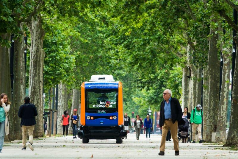 Los habitantes de la ciudad de Toulouse, paseo al lado de un mini autobús eléctrico autónomo, en la explanada Alain Savay Este tr foto de archivo