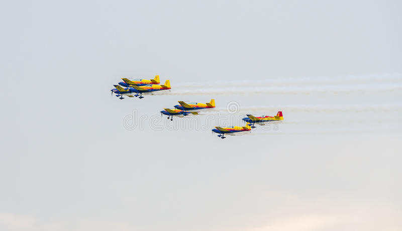 Los halcones rumanos combinan a los pilotos con sus aeroplanos coloreados que entrenan en el cielo azul imagen de archivo