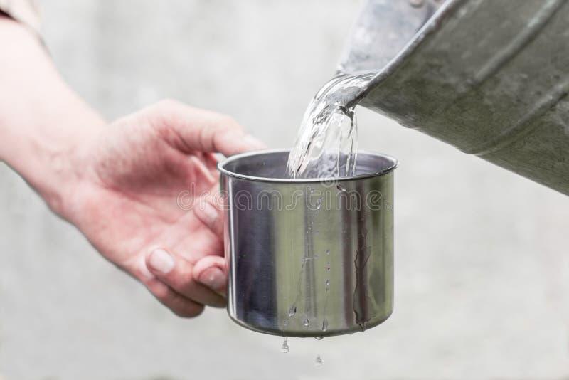 Los helds de la mano de Man's una taza de acero y un agua bien están vertiendo de un cubo imagen de archivo