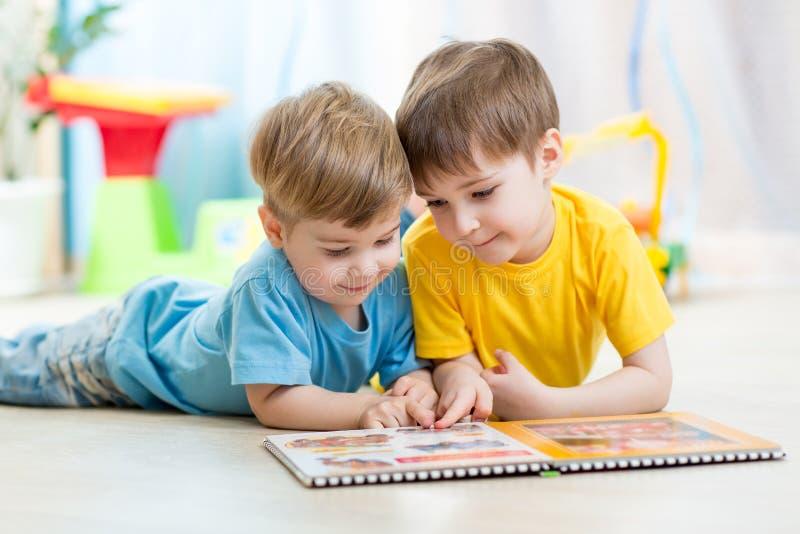 Los hermanos de niños leyeron un libro en casa imagenes de archivo