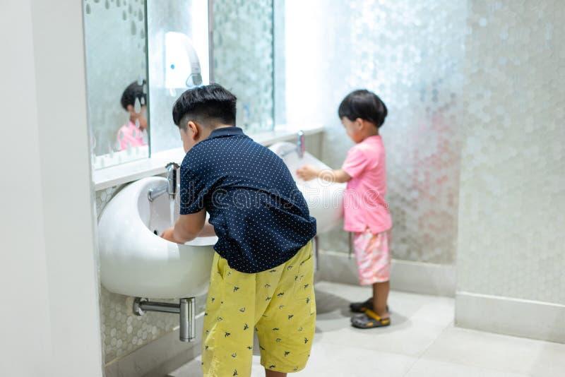 Los hermanos felices están lavando las manos en el retrete del niño imagen de archivo libre de regalías