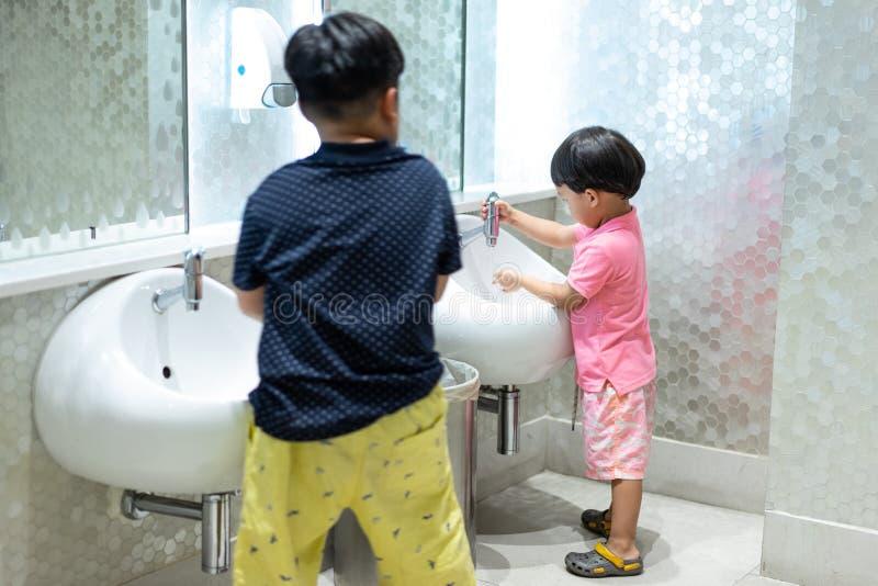 Los hermanos felices están lavando las manos en el retrete del niño foto de archivo