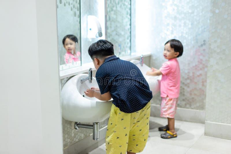 Los hermanos felices están lavando las manos en el retrete del niño foto de archivo libre de regalías
