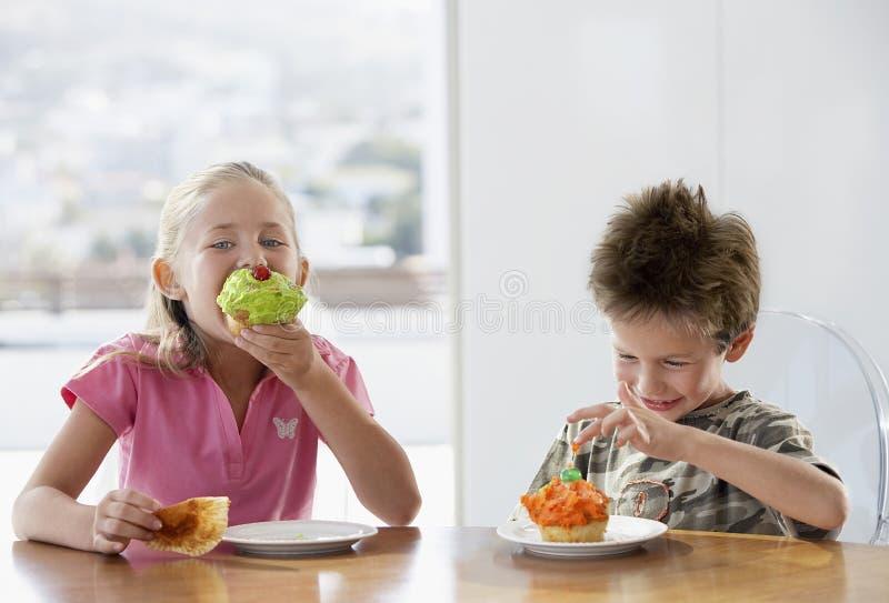 Los hermanos felices que comen la taza se apelmazan en la mesa de comedor imagen de archivo libre de regalías