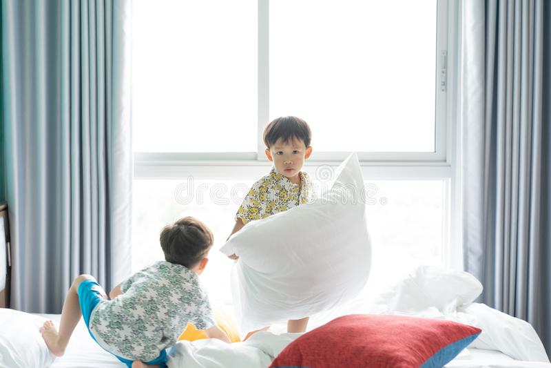 Los hermanos son de salto y que juegan por la mañana en la cama fotografía de archivo