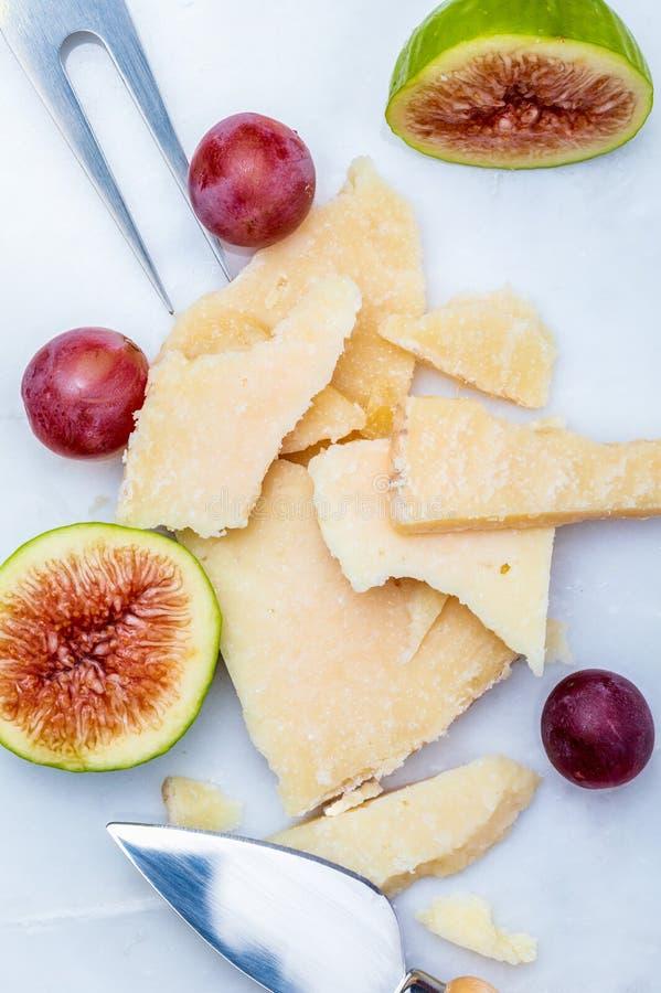 Los higos, las uvas rojas y el manchego del queso del ` s de las ovejas mecanograf?an fotos de archivo libres de regalías