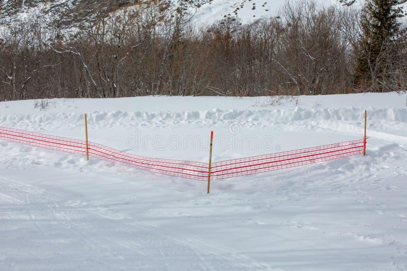 Los hitos de las carreteras y una red roja indican una sección peligrosa de la ruta en las montañas Noruega fotos de archivo libres de regalías