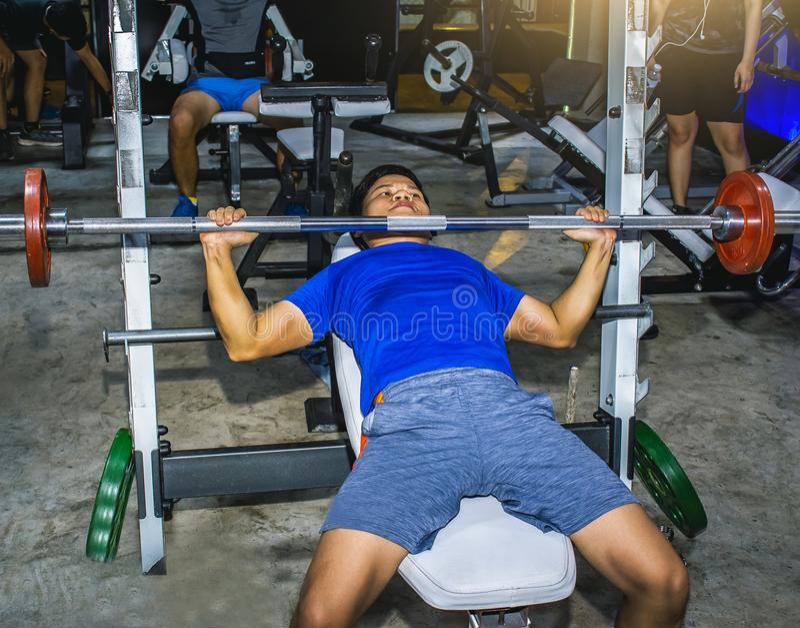Los hombres asiáticos ejercitan entrenamiento del pecho en lifestyl de la máquina de la prensa de banco imagenes de archivo