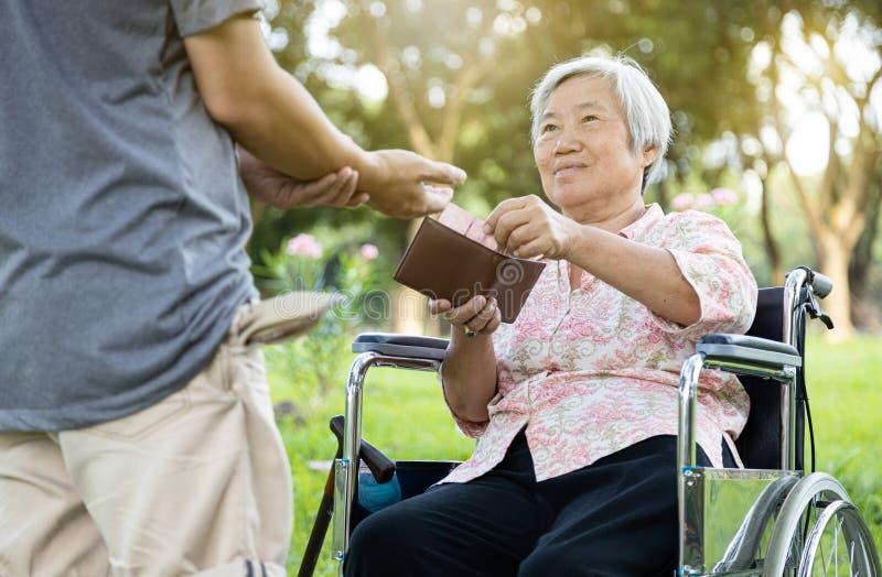 Los hombres asiáticos tienen un problema de dinero, piden dinero, los desempleados piden dinero a las mujeres mayores, la madre s fotos de archivo libres de regalías