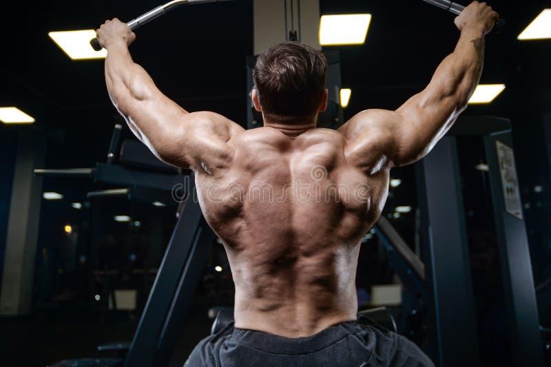 Los hombres atléticos del culturista fuerte brutal que bombean para arriba muscles con d fotografía de archivo
