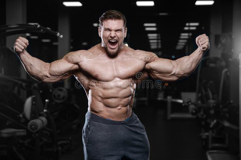 Los hombres atléticos del culturista fuerte brutal que bombean para arriba muscles con d foto de archivo