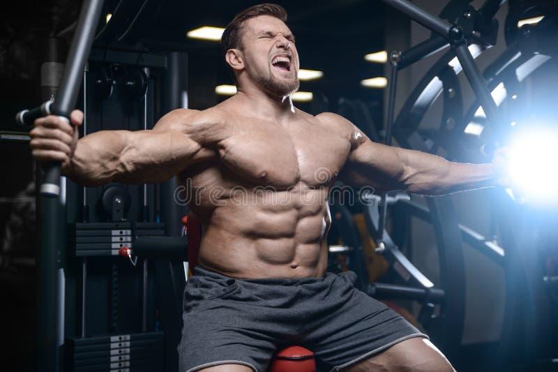 Los hombres atléticos del culturista fuerte brutal que bombean para arriba muscles con d fotos de archivo libres de regalías