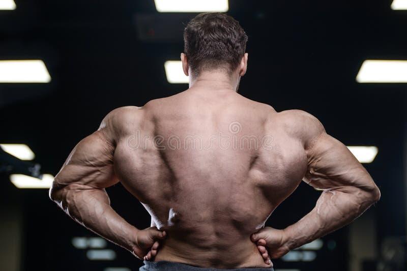 Los hombres atléticos del culturista fuerte brutal que bombean para arriba muscles con d fotos de archivo