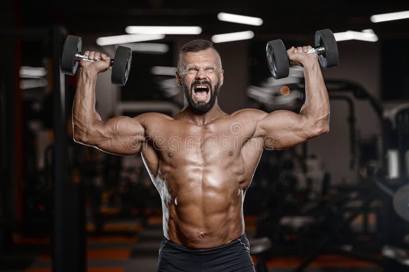 Los hombres atléticos del viejo culturista fuerte brutal que bombean para arriba muscles los wi imagenes de archivo
