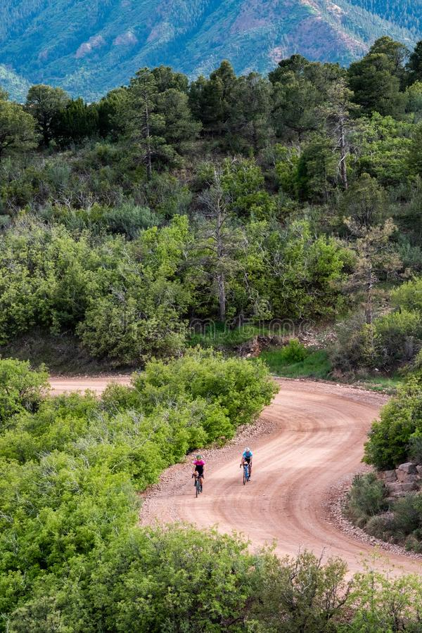 Los hombres biclying en lucios del camino de la montaña de la suciedad enarbolan la cordillera Colorado Springs imagenes de archivo