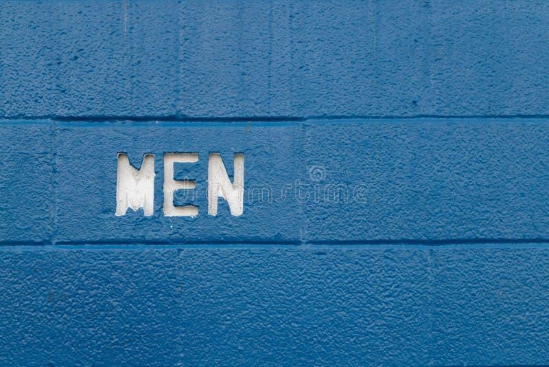 Los hombres blancos mandan un SMS al corte en los bloques de cemento azules imagen de archivo