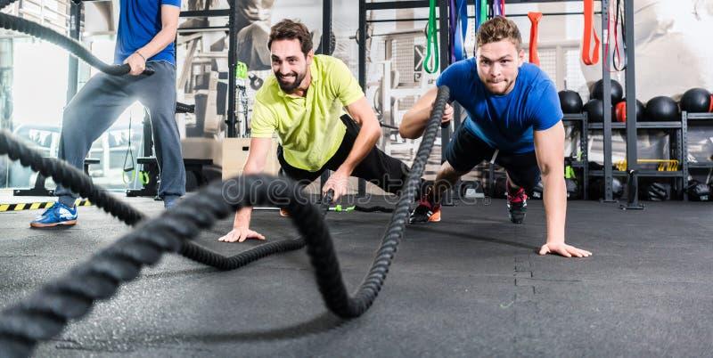 Los hombres con batalla rope en gimnasio funcional de la aptitud del entrenamiento fotos de archivo libres de regalías