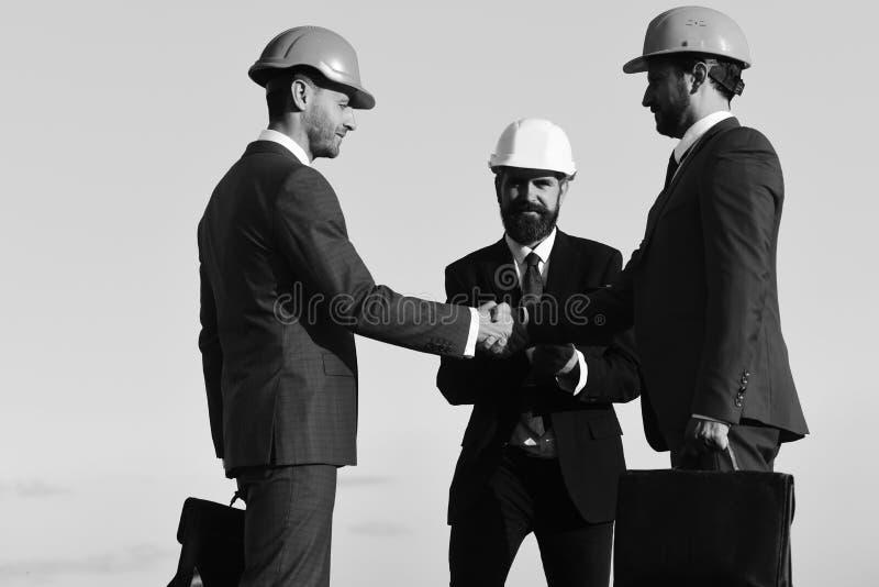 Los hombres con la barba y las caras ocupadas hacen el trato que sacude las manos foto de archivo libre de regalías