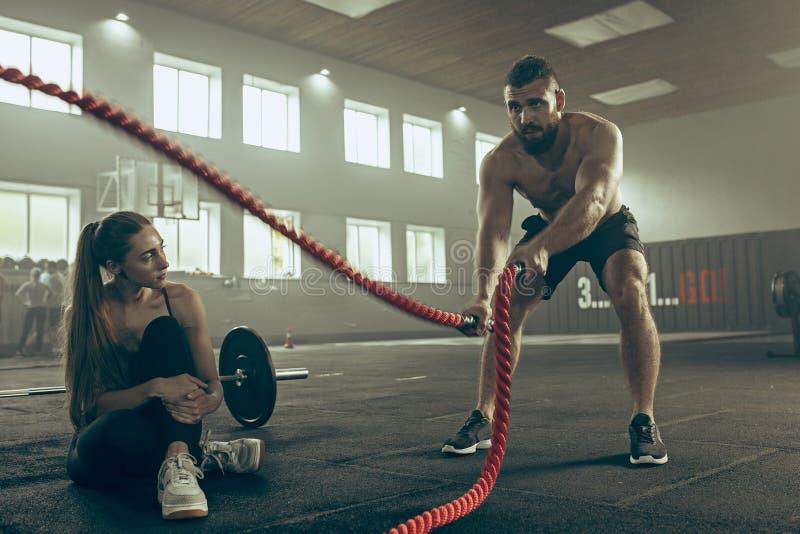 Los hombres con la cuerda de la batalla luchan cuerdas ejercitan en el gimnasio de la aptitud fotografía de archivo