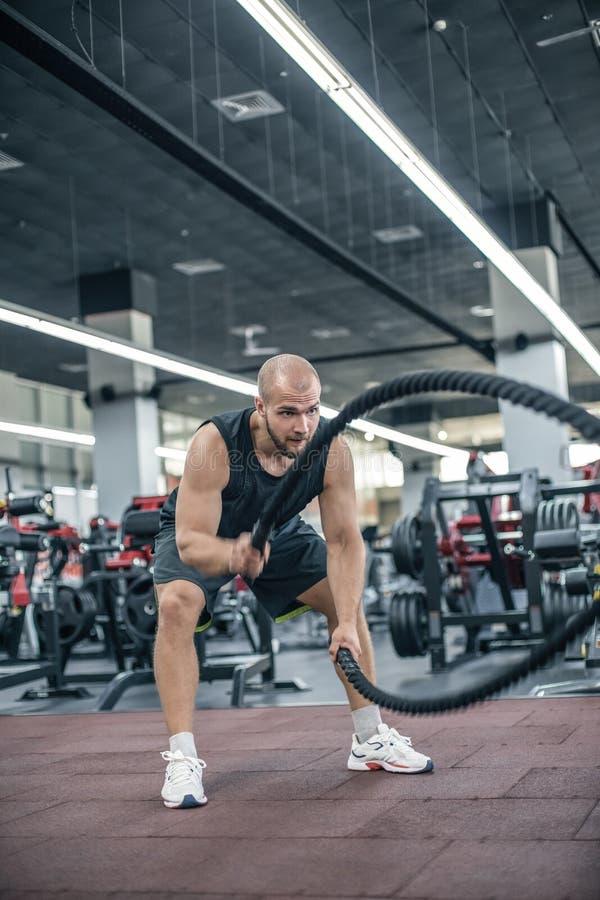 Los hombres con la cuerda de la batalla luchan cuerdas ejercitan en el gimnasio de la aptitud Crossfit fotografía de archivo libre de regalías