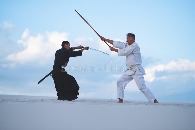 Los hombres concentrados, en ropa japonesa, están practicando artes marciales foto de archivo libre de regalías