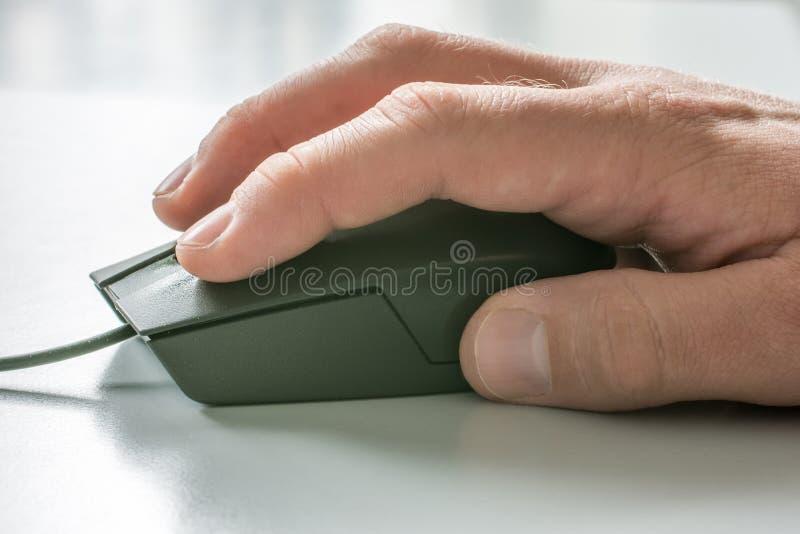 Los hombres dan en ratón del ordenador con el escritorio blanco en el fondo fotos de archivo libres de regalías