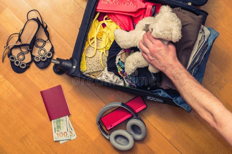 Los hombres dan poner el oso de peluche en una maleta Cuentas extranjeras del pasaporte y del ciento-dólar para el viaje Concepto fotos de archivo