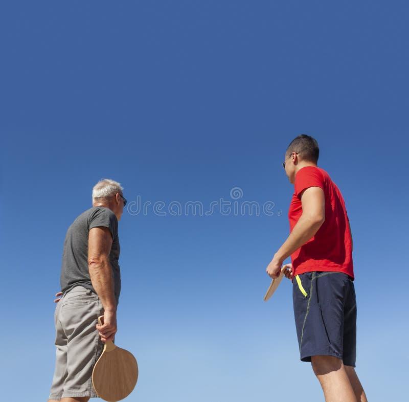Los hombres de diversas generaciones juegan a tenis de la playa imagen de archivo libre de regalías