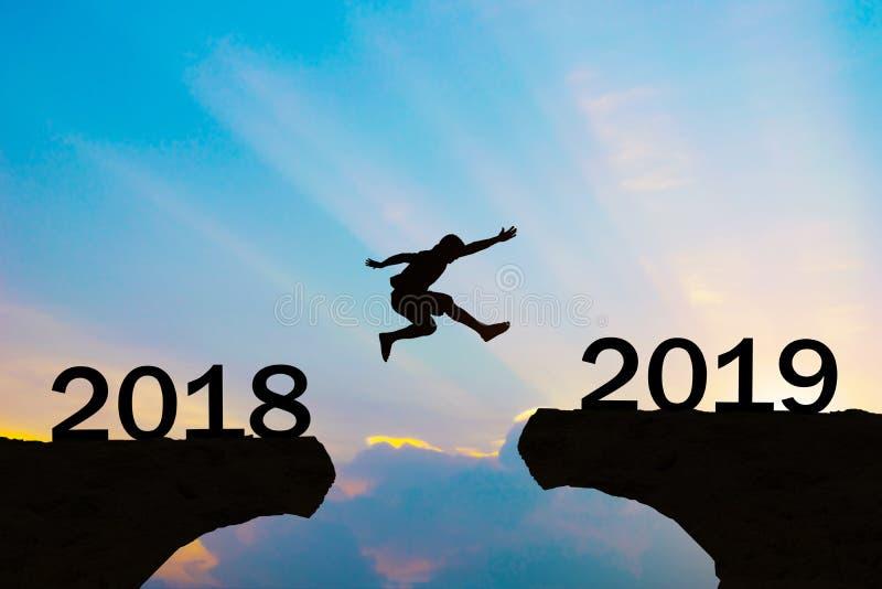 Los hombres de la Feliz Año Nuevo 2019 saltan sobre las montañas de la silueta imagenes de archivo