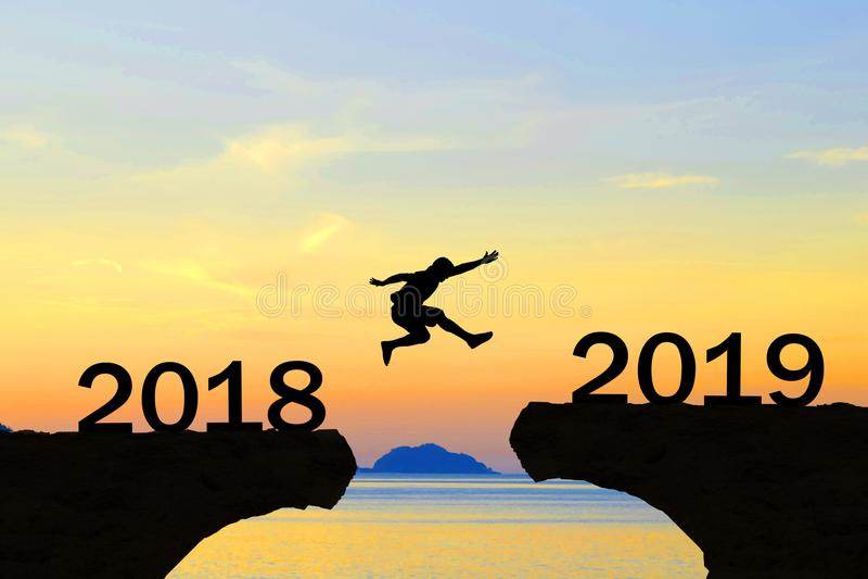 Los hombres de la Feliz Año Nuevo 2019 saltan sobre silueta imagen de archivo libre de regalías