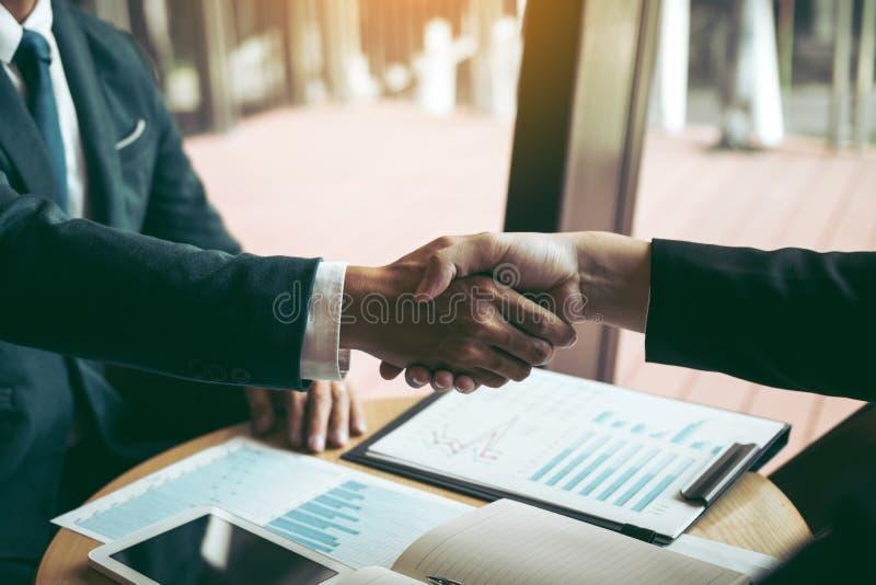 Los hombres de negocios aceptan o confirman proyecto sobre la oferta y se unen a la sacudida de las manos en la compa??a del siti foto de archivo