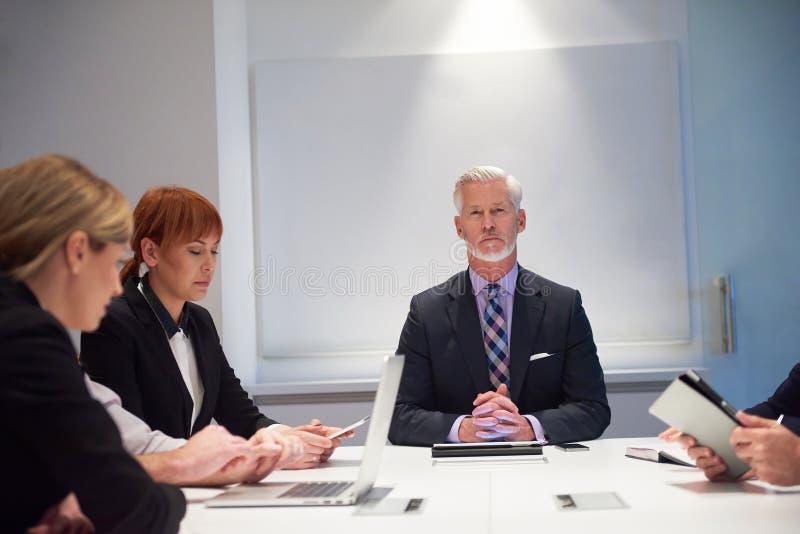 Los hombres de negocios agrupan en la reunión foto de archivo