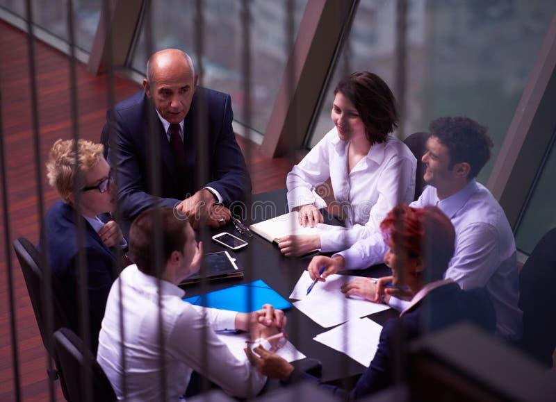 Los hombres de negocios agrupan en la reunión en la oficina brillante moderna fotografía de archivo