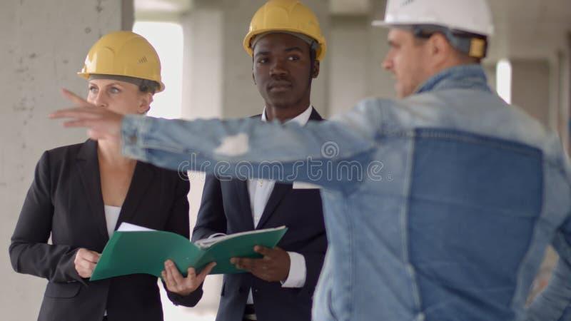 Los hombres de negocios agrupan en la reunión y la presentación en emplazamiento de la obra con el arquitecto y el trabajador del foto de archivo libre de regalías