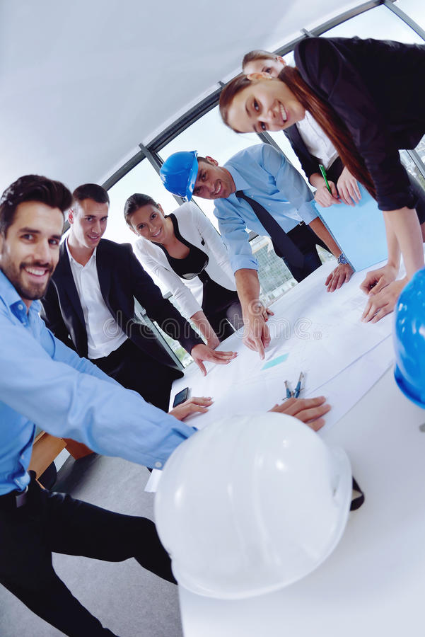 Los hombres de negocios agrupan en una reunión en la oficina imagen de archivo